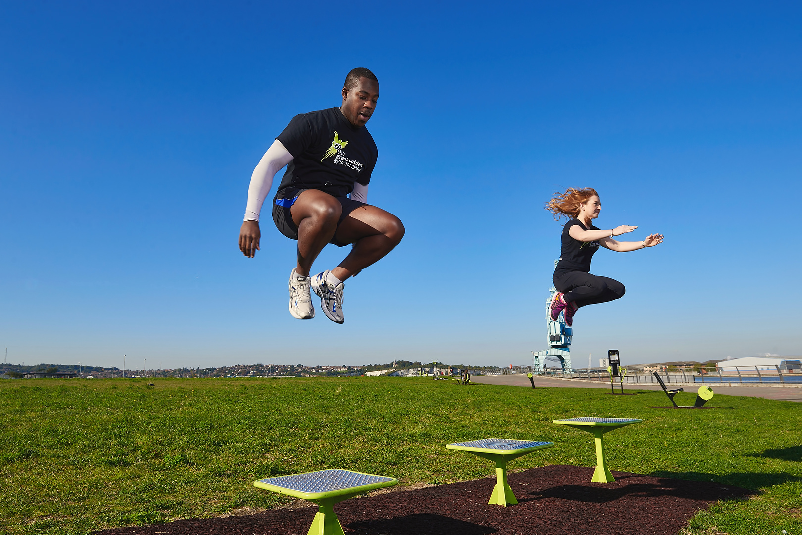 two people jumping from an outdoor gym platform
