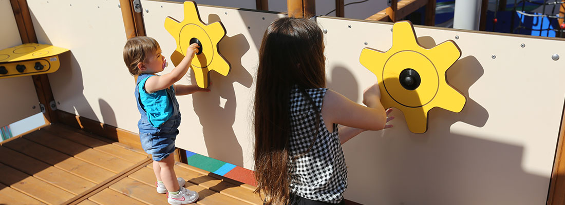 Girls playing with the ship's wheel on a pirate themed multi-play unit